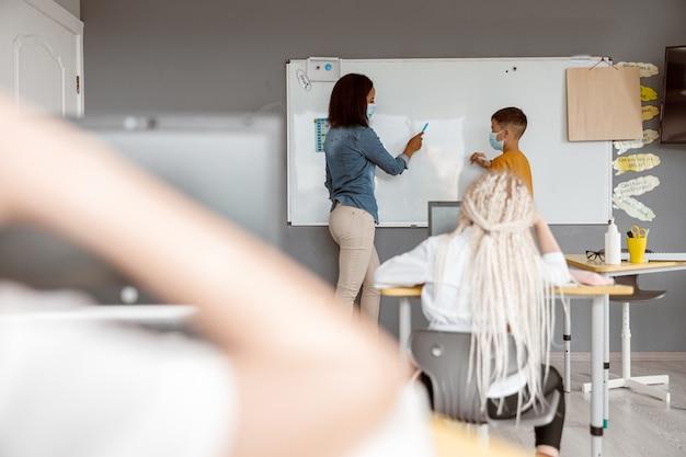 교실에서 칠판 근처에 서 있는 젊은 교사와 소년