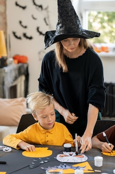 Young teacher in black pullover and witch hat pointing at skull picture