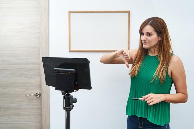 若い先生がビデオ通話で自宅でオンラインクラスを与えます。オンラインでの新技術、学習、授業のコンセプト。