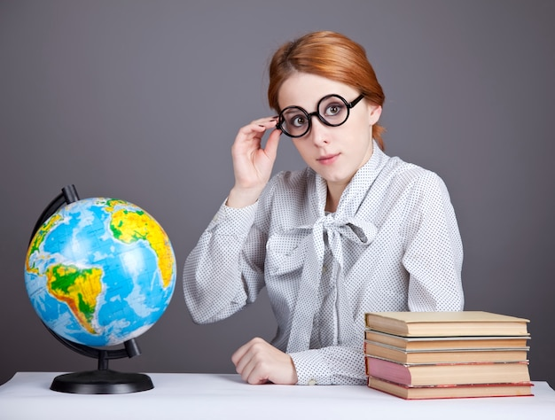 The young teacher in glasses with books and globe