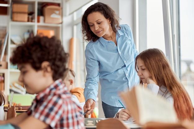 젊은 교사가 학생을 읽는 데 도움을줍니다. 책상에 앉아 교실에서 책을 읽는 초등학교 아이들.