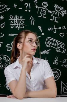 Молодой учитель сидит возле доски в классе