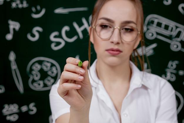 若い先生は教室の黒板の近くに座っています