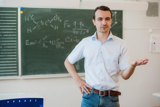 Молодой учитель возле доски в школьном классе разговаривает с классом