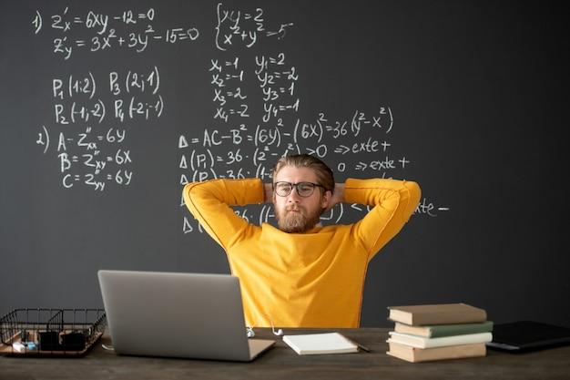 Молодой учитель или ученик в повседневной одежде смотрит на дисплей ноутбука во время онлайн-урока алгебры, держа руки на затылке