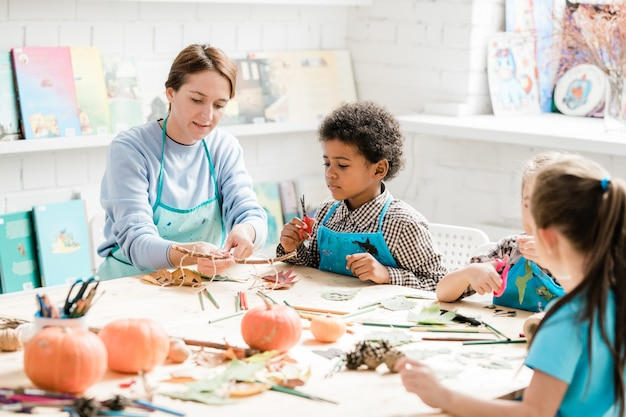 Young teacher pointing at stick with several halloween decorations bound to it with threads while showing them to group of classmates