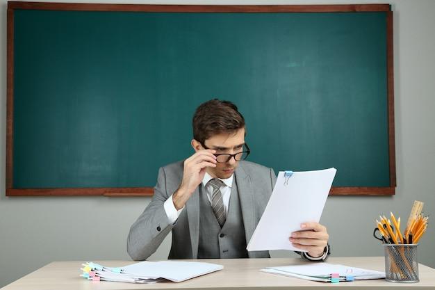 学校の教室に座っている若い先生