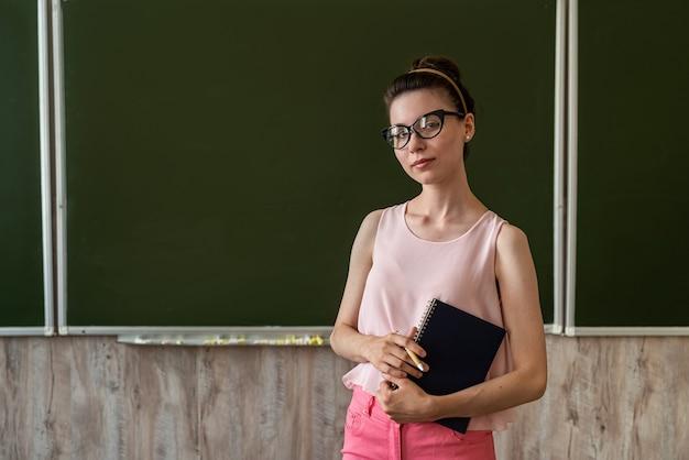 빈 칠판 근처에 서서 새로운 수업을 설명하는 젊은 교사