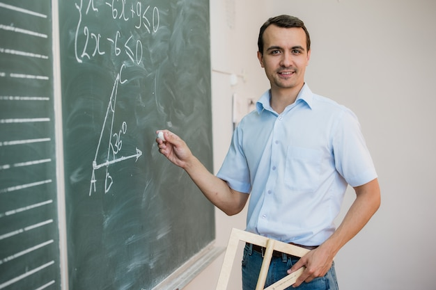 Young teacher or student holding triangle pointing at chalkboard with formula