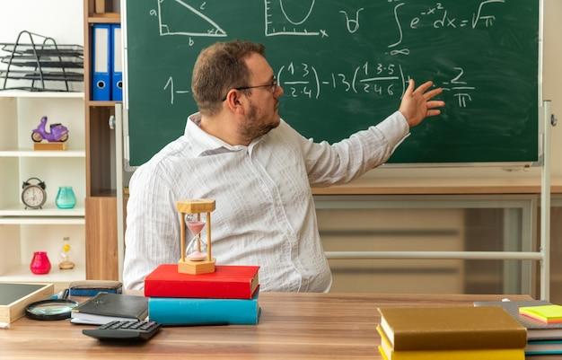 Giovane insegnante con gli occhiali seduto alla scrivania con materiale scolastico in classe guardando la lavagna indicandola con la mano
