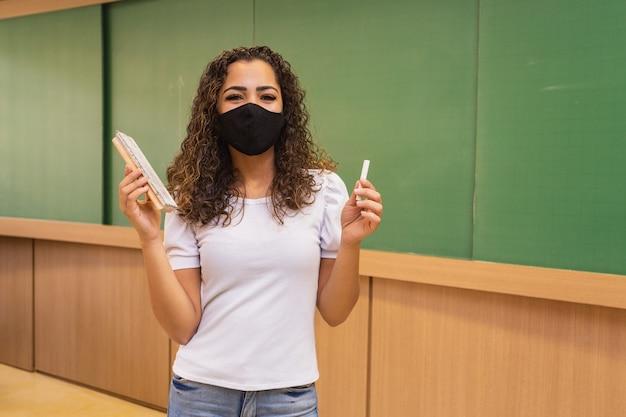 분필과 지우개를 손에 들고 외과용 마스크를 쓰고 있는 젊은 교사.