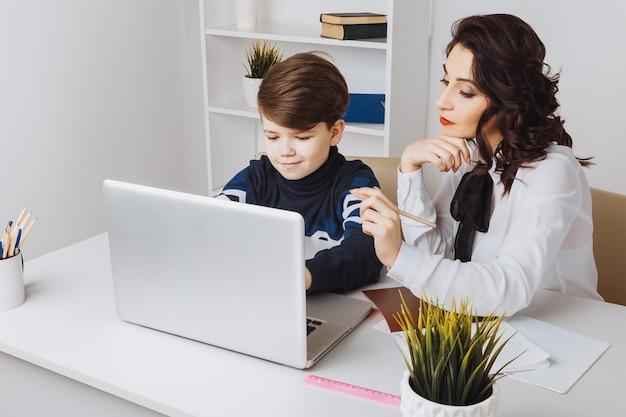 コンピューターで宿題をしている子供と若い先生。家庭教師の助け。