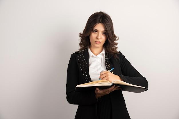 그녀의 클래스에 대 한 메모를 작성 하는 젊은 교사.
