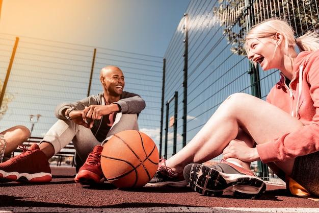 젊은 팀. 그녀의 친구에게 얘기하는 행복 한 어린 소녀 근처에 누워 농구 공