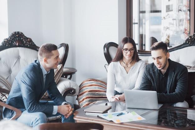 Молодая команда коллег делает большую деловую дискуссию в современном офисе коворкинг. концепция совместной работы людей