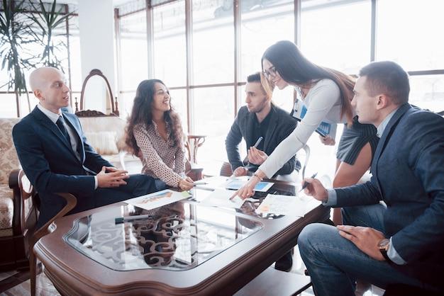 Молодая команда коллег, делая большую деловую дискуссию в современном офисе. концепция совместной работы людей