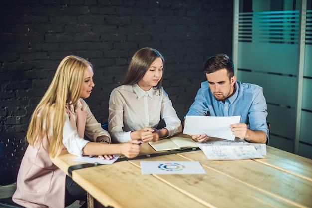 現代のコワーキングオフィスでビデオを撮影するためにストーリーボードを見ている同僚の若いチーム
