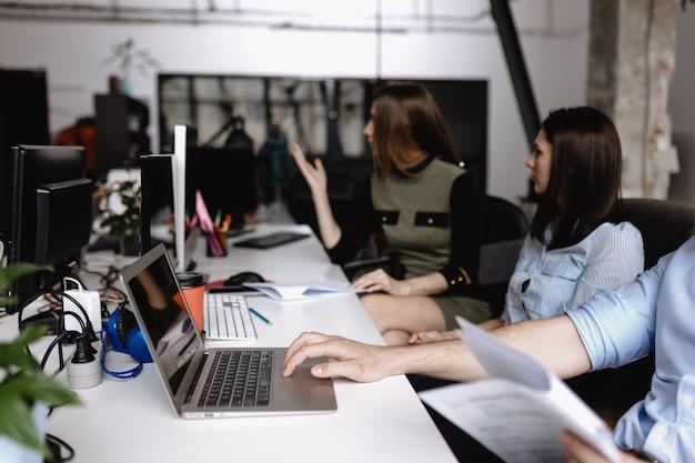 Молодая команда коллег сидит за столами с ноутбуком и документами в светлом современном офисе.