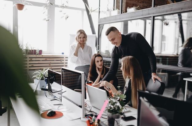 Молодая команда работает за столами с компьютером и ноутбуками в светлом современном офисе open space.