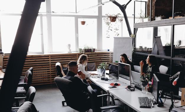 Молодая команда работает в просторном, светлом современном офисе open space, сидя за столами с компьютером и ноутбуками.