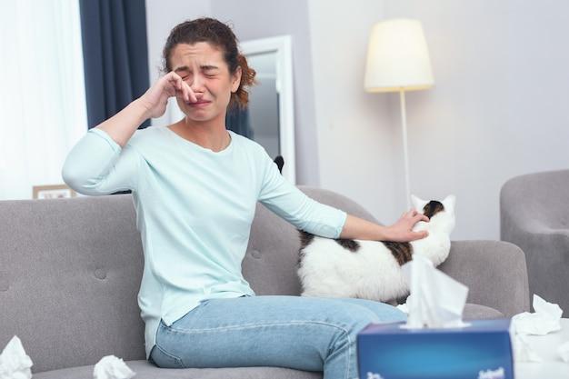 Молодая женщина со слезами на глазах ухаживает за своей кошкой, страдающей от первых симптомов аллергии на кошачий мех