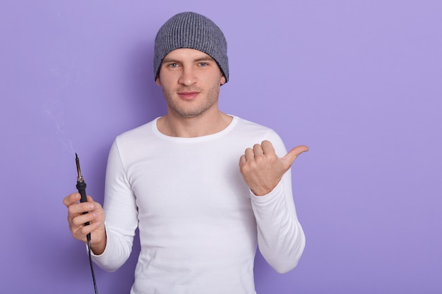 Young technician being ready to solder wire, attractive male wears white casual shirt and gray cap holds soldering iron in one hand and point aside with another thumb, isolated on purple.