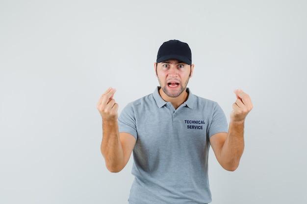 灰色の制服を着たばかげた質問に不満を持って、イタリアのジェスチャーをしている若い技術者。