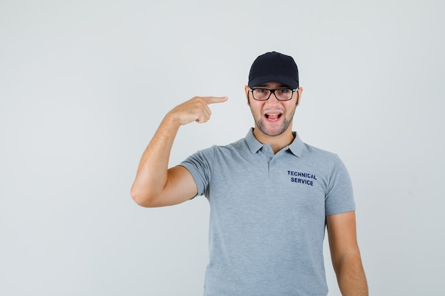 Young technician in grey uniform pointing at his glasses and looking joyful.