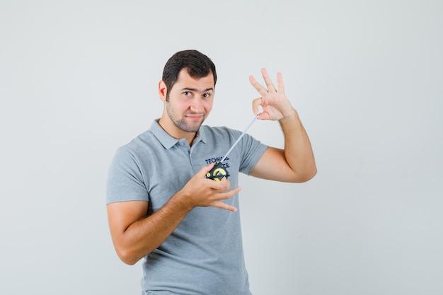 Giovane tecnico in uniforme grigia che mostra il metro a nastro mentre lo apre e sembra felice.