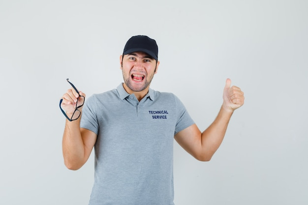 Young technician in grey uniform showing thumb up, holding glasses and looking happy.