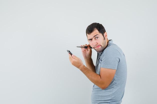 Giovane tecnico in uniforme grigia che cerca di aprire il suo smartphone usando il trapano e attaccando la lingua e guardando concentrato.
