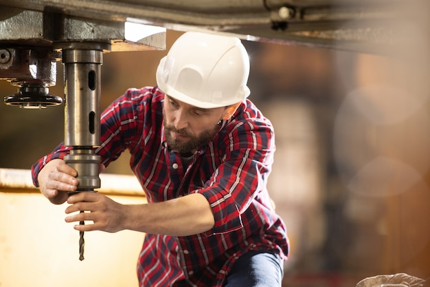 Young technician in hardhat and overalls putting drill element into iron holder which is part of large industrial machine