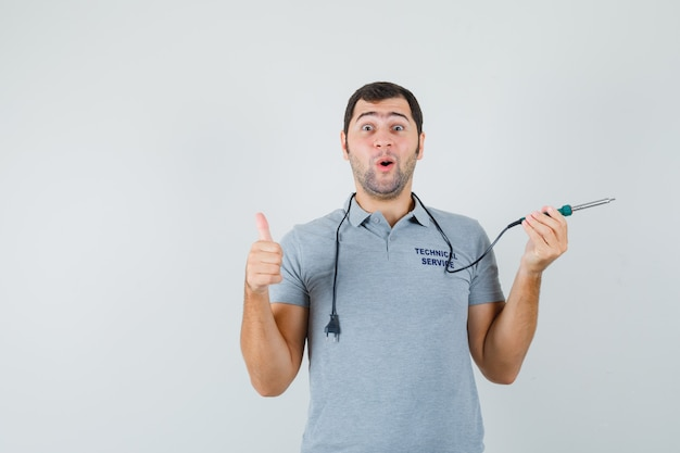 Giovane tecnico che tiene il trapano in una mano mentre mostra il pollice in uniforme grigia e sembra sorpreso.