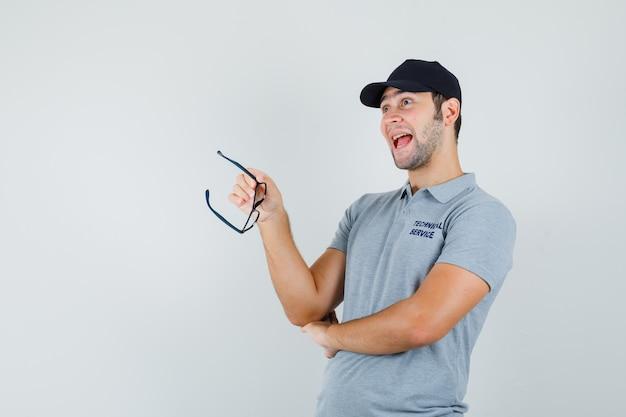 회색 유니폼과 낙관적 찾고 안경을 들고 젊은 기술자.