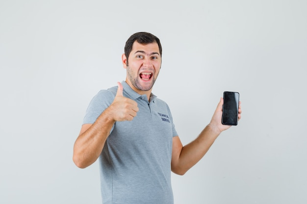 Young technician holding mobile phone, showing thumb up in grey uniform and looking blissful , front view.