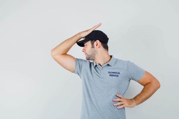 젊은 기술자는 머리에 한 손을 잡고 회색 유니폼을 입고 허리에 다른 손을 잡고 실망했습니다.