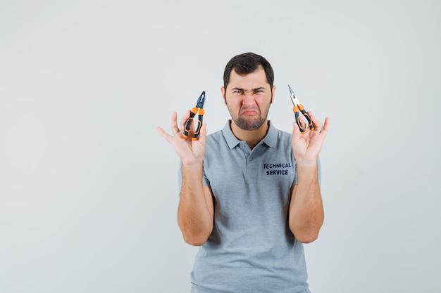 Giovane tecnico che tiene le pinze in entrambe le mani in uniforme grigia e sembra scontento.