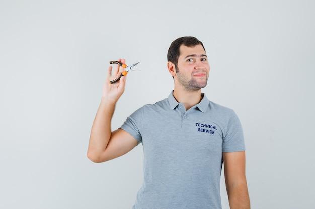 Giovane tecnico che tiene le pinze in uniforme grigia e che sembra fiducioso. vista frontale.