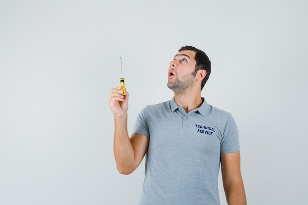 Young technician holding screwdriver in grey uniform and looking amazed.