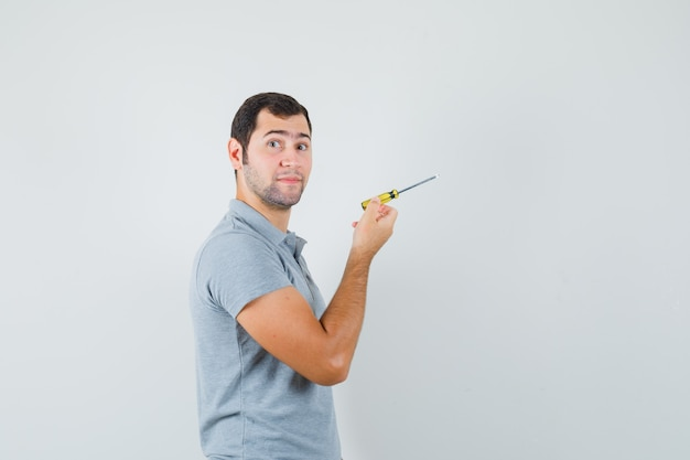 Young technician holding screwdriver and posing in grey uniform and looking focused.
