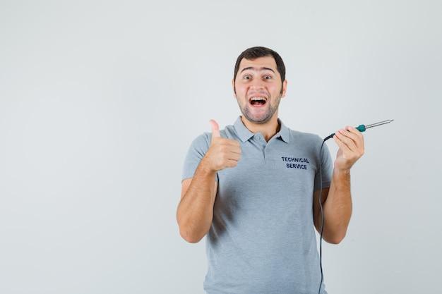 Giovane tecnico che tiene un cacciavite e mostra il pollice in su in uniforme grigia e sembra soddisfatto.
