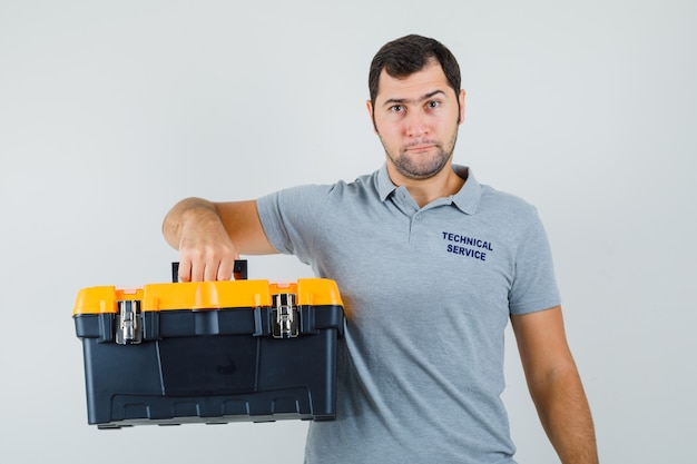 Young technician holding toolbox in grey uniform and looking serious.