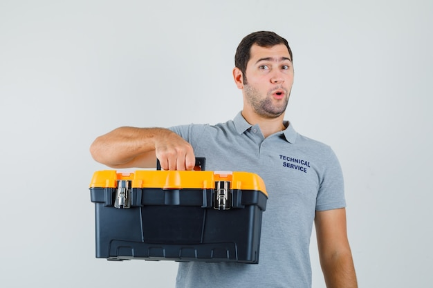 Young technician holding toolbox in grey uniform and looking surprised.