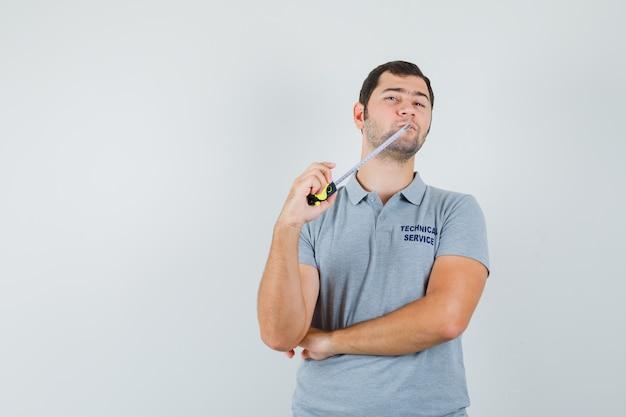 灰色の制服をかむ巻尺の若い技術者と思考ポーズで立って物思いにふける。