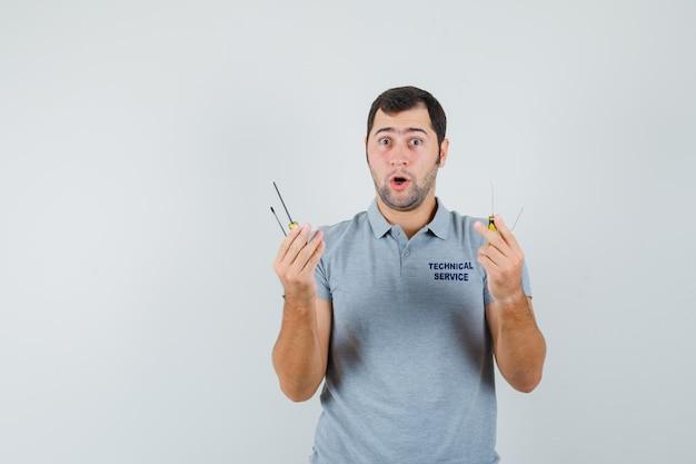 Молодой техник в серой униформе держит отвертки и выглядит удивленным
