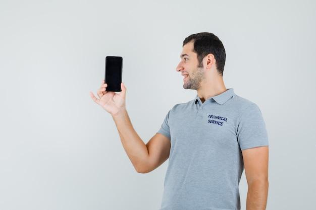 灰色の制服を着た若い技術者がスマートフォンを手に持って、それを見て、楽観的な正面図を見て笑っています。