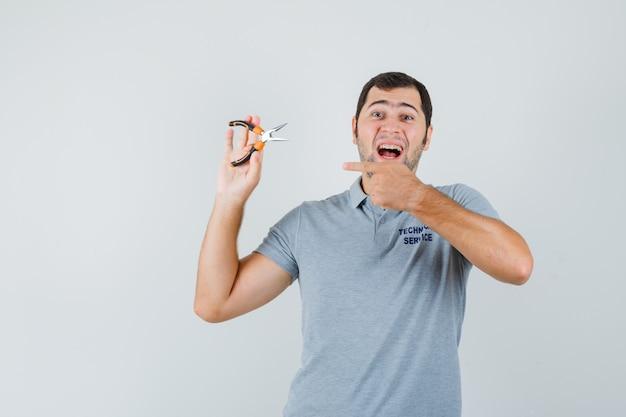 ペンチを指して、嬉しそうに見える灰色の制服を着た若い技術者、正面図。