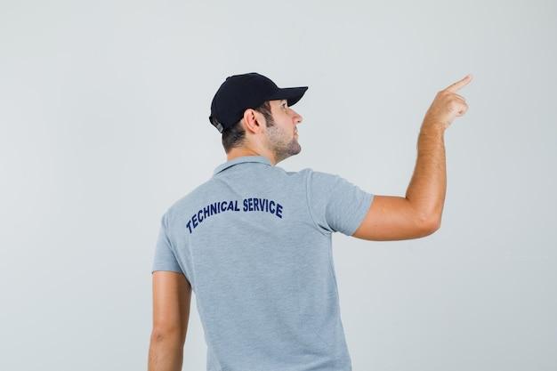 Молодой техник в серой форме, указывая на верхний правый угол и глядя сосредоточенно, вид сзади.