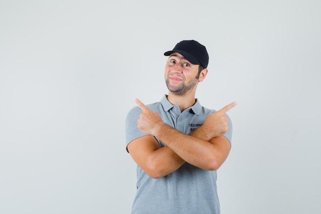 灰色の制服を着た若い技術者が指を指さし、陽気に見えます。