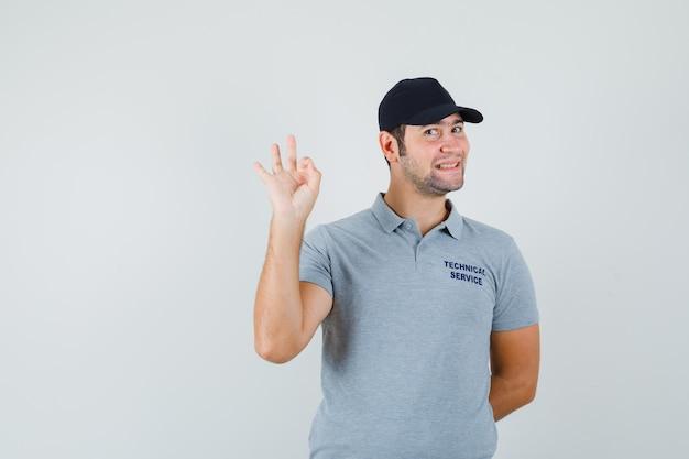 Молодой техник в серой форме демонстрирует жест и уверенно выглядит.